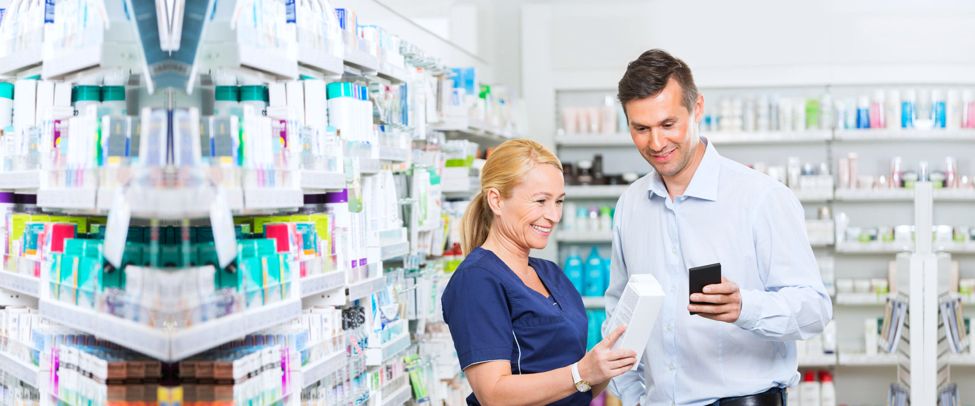 Smiling male customer using mobile phone and a pharmacist