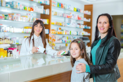 Pharmacist giving vitamins to a child in drugstore